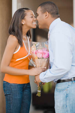 rubbing noses: African couple rubbing noses over bouquet of flowers