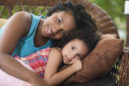 rubbing noses: African mother and daughter laying on sofa
