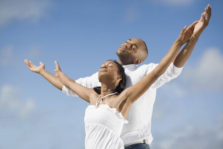 human being: Multi-ethnic couple with arms raised LANG_EVOIMAGES