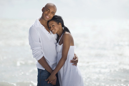 gusto: Multi-ethnic couple hugging at beach LANG_EVOIMAGES