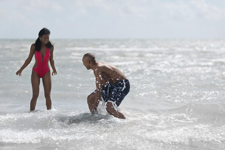 Multi-ethnic couple playing in water