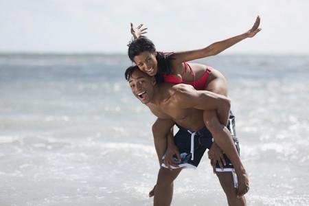 African man giving girlfriend piggy back ride 免版税图像