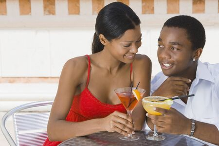 smooching: Multi-ethnic couple toasting with cocktails LANG_EVOIMAGES