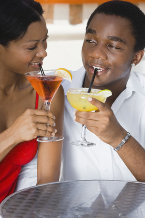 wooing: Multi-ethnic couple drinking cocktails LANG_EVOIMAGES