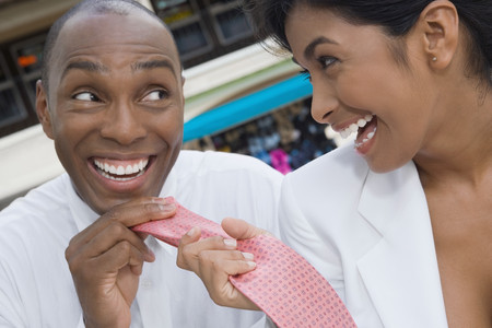 typist: Hispanic woman pulling boyfriend's necktie