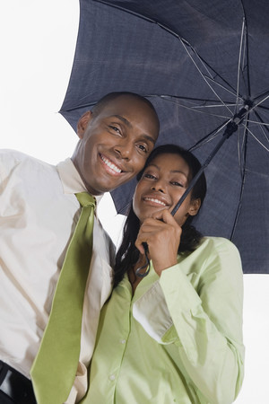 Hispanic couple standing under umbrella