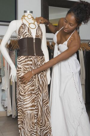smooching: African woman adjusting dress on mannequin