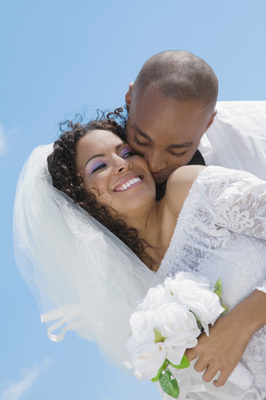 Multi-etnische bruid en bruidegom knuffelen Stockfoto