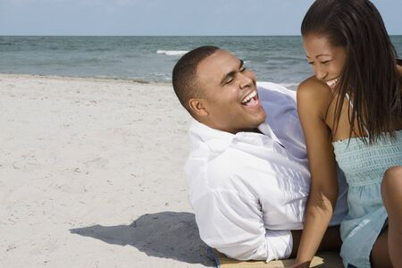 low spirited: African couple laughing at beach