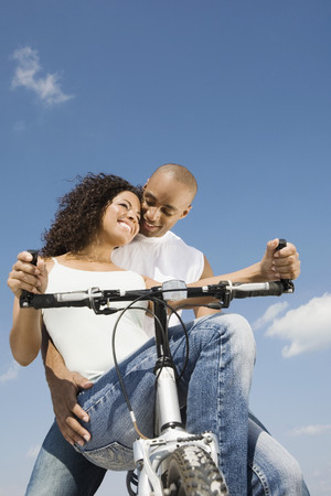 clear day in winter time: Multi-ethnic couple sitting on bicycle