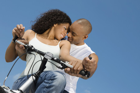 searcher: Multi-ethnic couple sitting on bicycle