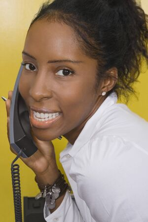 unyielding: African woman talking on telephone LANG_EVOIMAGES