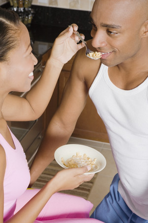 challis: African woman feeding cereal to husband LANG_EVOIMAGES