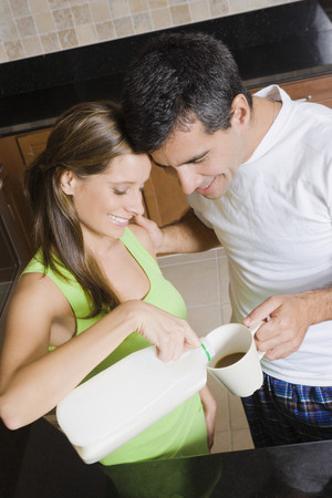 challis: Hispanic woman pouring milk in husband's coffee