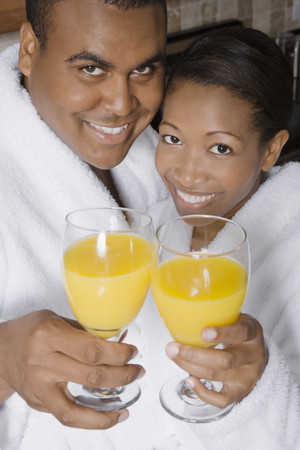 challis: African couple toasting with orange juice LANG_EVOIMAGES