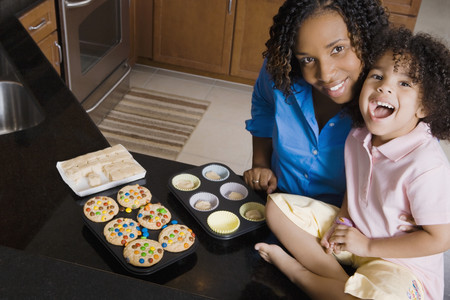 talker: African mother and daughter making cupcakes LANG_EVOIMAGES
