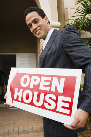 Hispanic real estate agent holding Open House sign Stock Photo
