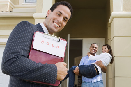 milepost: Hispanic real estate agent and African couple in front of house