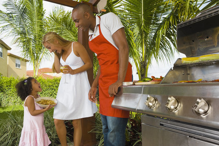 one family: Mixed Race family barbecuing