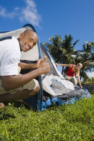 lighthearted: Multi-ethnic couple setting up tent LANG_EVOIMAGES