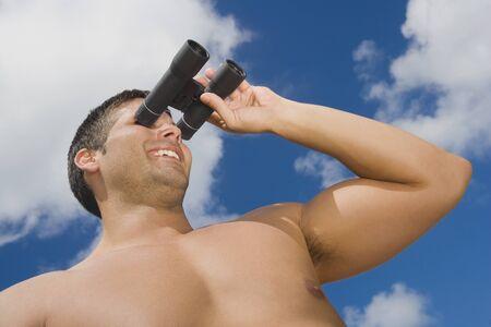 unconcerned: Hispanic man looking through binoculars