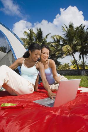 adventuresome: Hispanic women looking at laptop LANG_EVOIMAGES