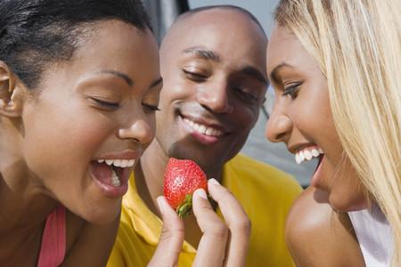 munching: Hispanic woman eating strawberry LANG_EVOIMAGES