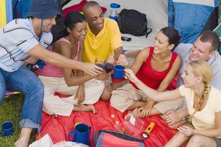 adventuresome: Multi-ethnic friends toasting at campsite