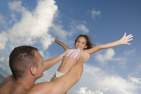 elementary age girl: Father holding daughter in air LANG_EVOIMAGES