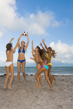 bathingsuit: Multi-ethnic girls playing with soccer ball at beach