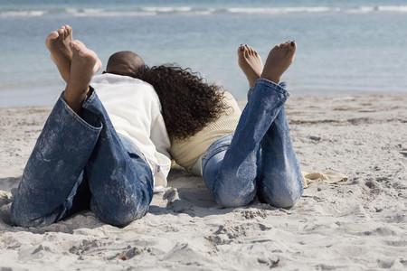 Multi-ethnic couple laying on beach