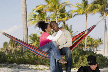 Hispanic couple hugging in hammock