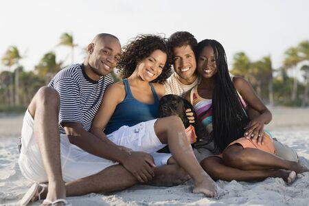 Multi-ethnic couples sitting on beach Stock Photo