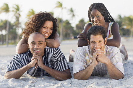 vacationing: Multi-ethnic couples laying on beach