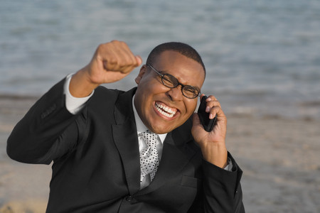 talker: African businessman cheering on cell phone LANG_EVOIMAGES