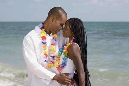 honeymooner: African couple hugging at beach