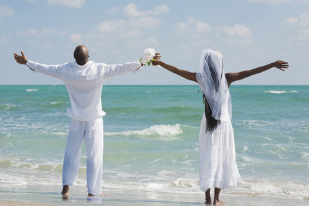 milepost: African bride and groom with arms outstretched