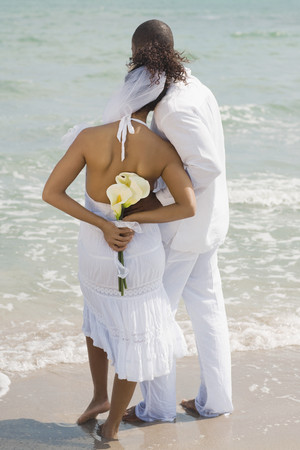milepost: Multi-ethnic bride and groom at beach LANG_EVOIMAGES