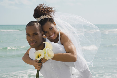 Multi-ethnic bride and groom hugging at beach Stockfoto