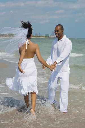 away from it all: Multi-ethnic bride and groom walking in ocean surf LANG_EVOIMAGES