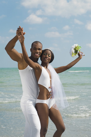 African bride and groom hugging at beach Stock Photo