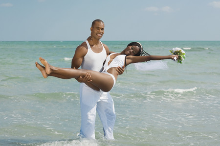 African groom carrying bride at beach Imagens