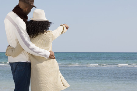 Multi-ethnic couple hugging and pointing at beach