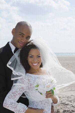 lighthearted: Multi-ethnic bride and groom hugging LANG_EVOIMAGES