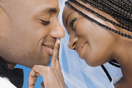 african descent ethnicity: African bride touching groom's lips