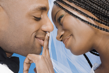 veils: African bride touching groom's lips LANG_EVOIMAGES