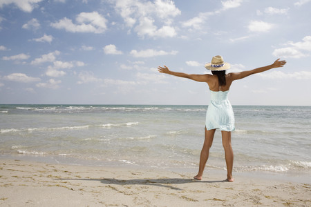 talker: African woman with arms outstretched at beach LANG_EVOIMAGES