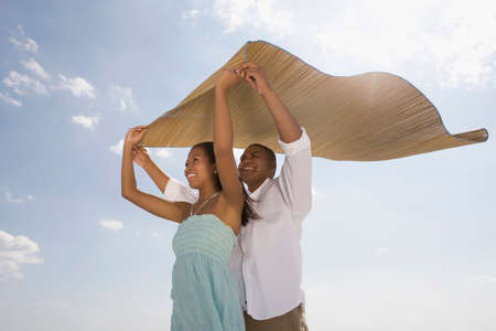 African couple holding mat in wind