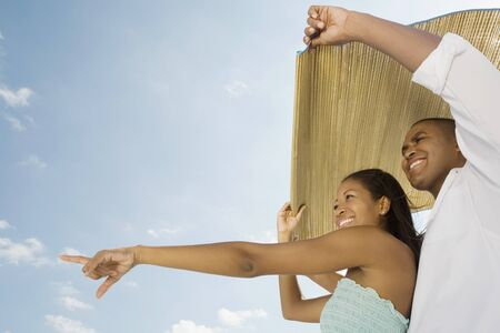 low spirited: African couple holding mat in wind