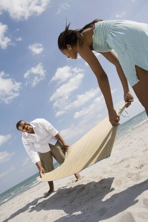 gusto: African couple laying mat on sand